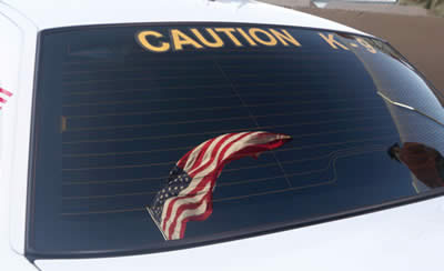 Flag in the window of a police car signifying the honorable service of the K9 Teams.